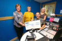 At WaveFM today are Kay Allardice, left, and Margaret McRae handing over the cheque for £1,000 raised from donations, instead of birthday presents, for Help For Kids to mid morning WaveFM DJ Craig Lumsden, with Stacey Wallace, right , Help For Kids Charity Manager.