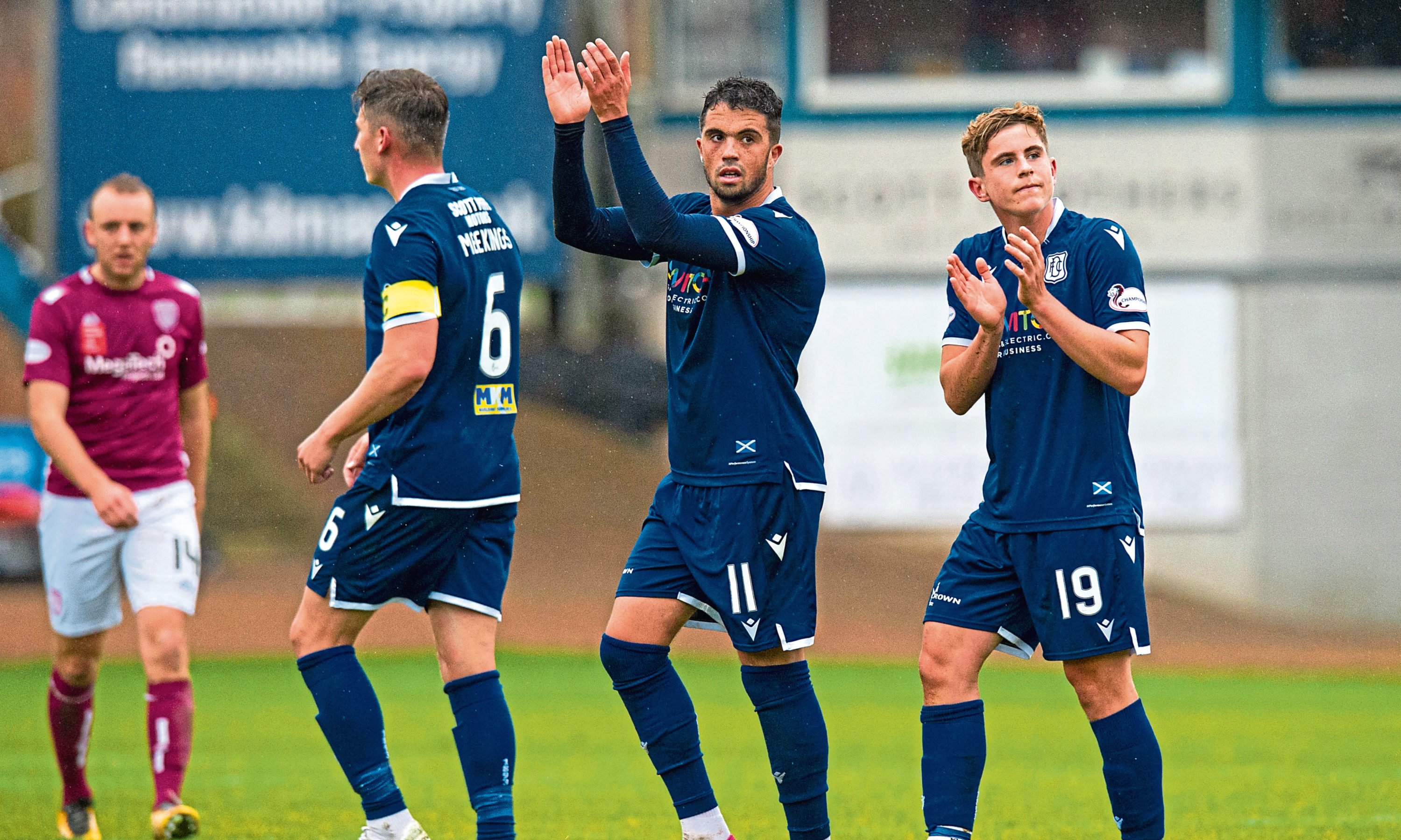 Dundee's Declan McDaid, centre, and Finlay Robertson applaud home fans during the match between Dundee and Arbroath at the Kilmac Stadium on Saturday.