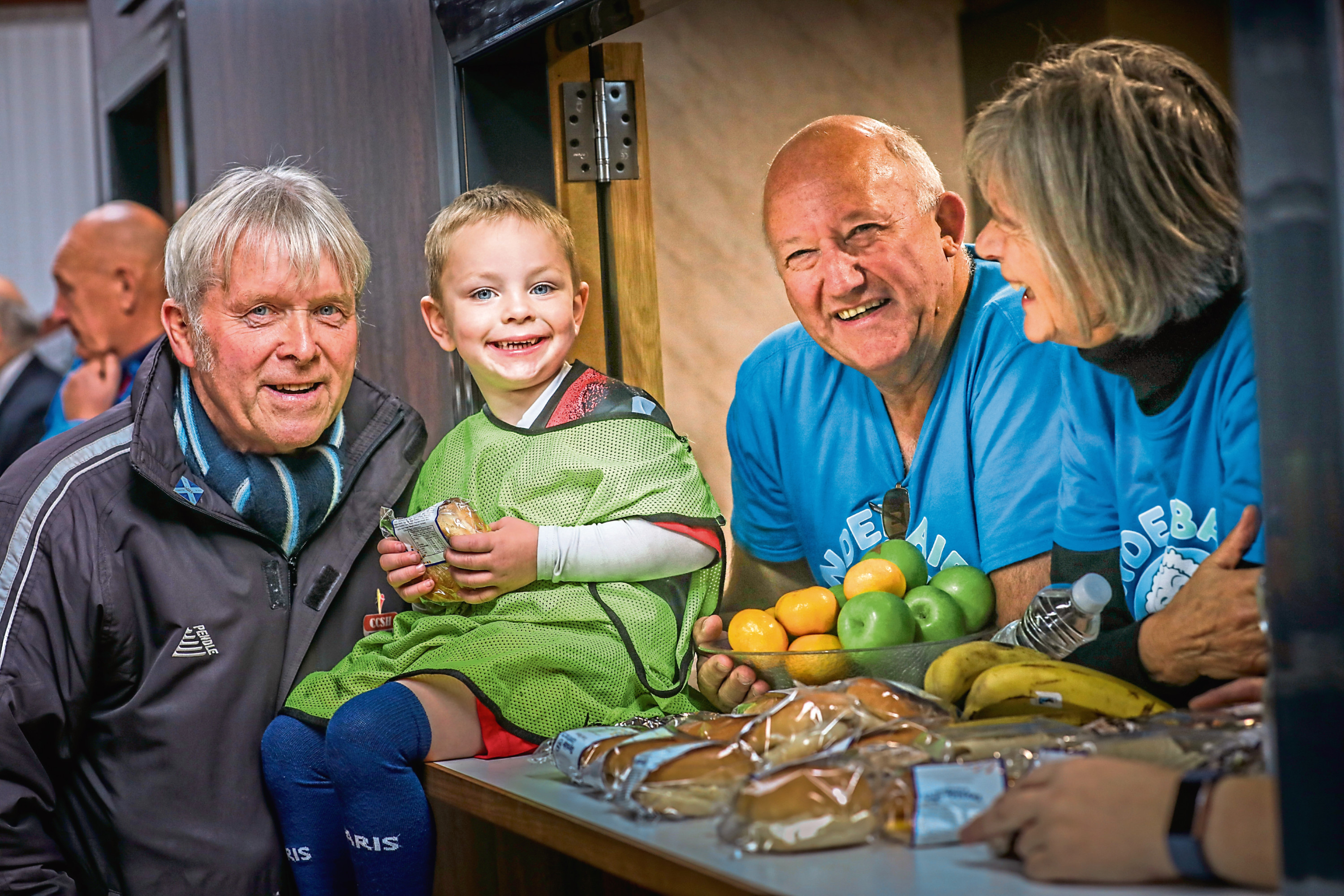 David Dorward and Jacquie Roberts, dish out the lunch to Caleb Sturrock, 4, and Jim McIlravey, President of the sports club.