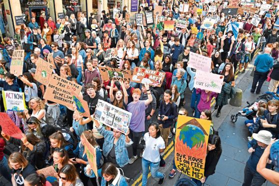 Protesters march and hold placards as they attend the Global Climate Strike on September 20.