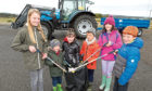 Isla Rae, Cayle Dolan, Tilly Dolan, Rufus McKinnel, Keira Lammond and Anton Rae standing in front of the beach clean-up tractor.
