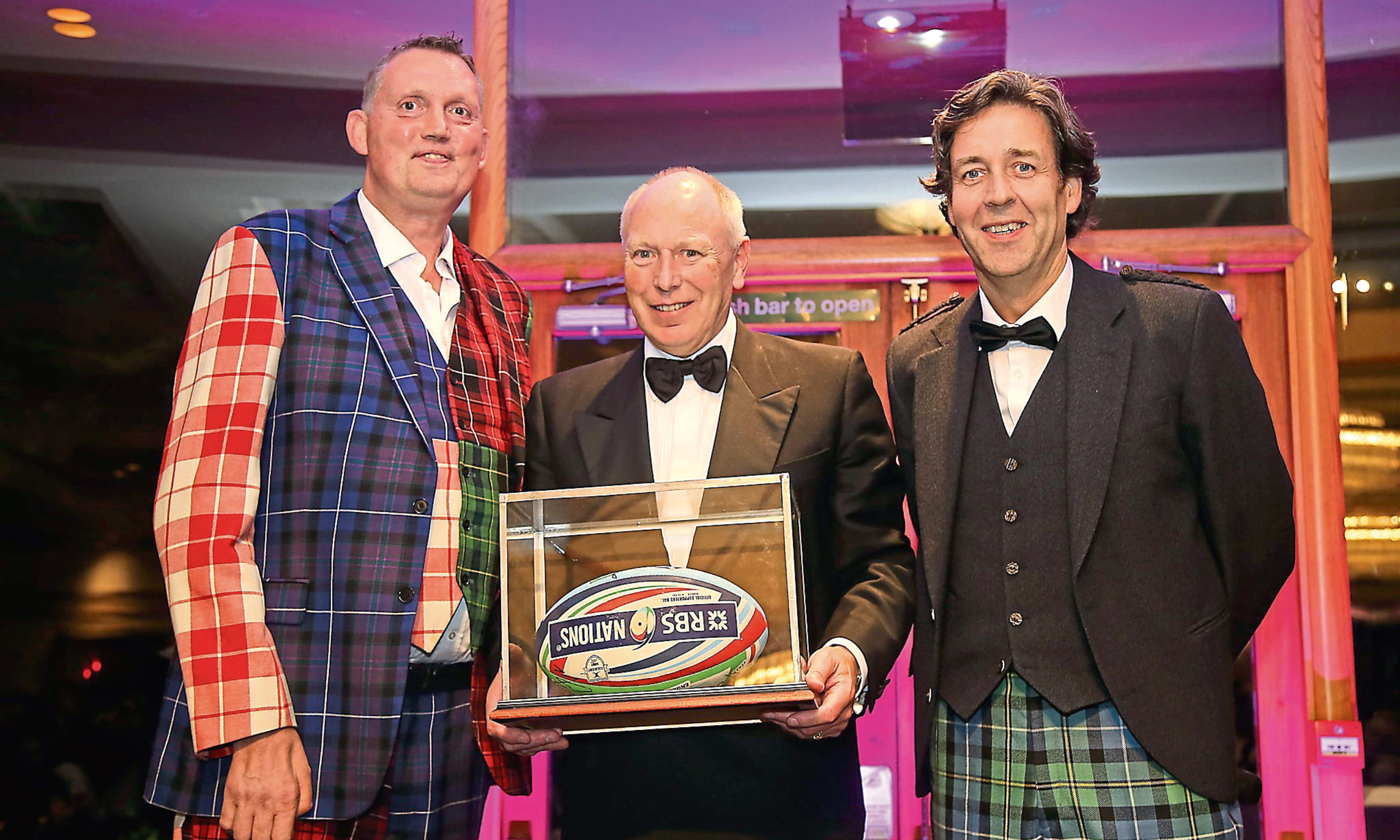 Robin Porter with the signed ball and Doddie Weir (left) and Stephen Webster, chief executive of Thorntons Investments.