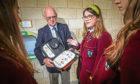 A defibrillator being installed at Harris Academy.