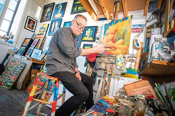Jonathan Hood inside his studio space with examples of his work.