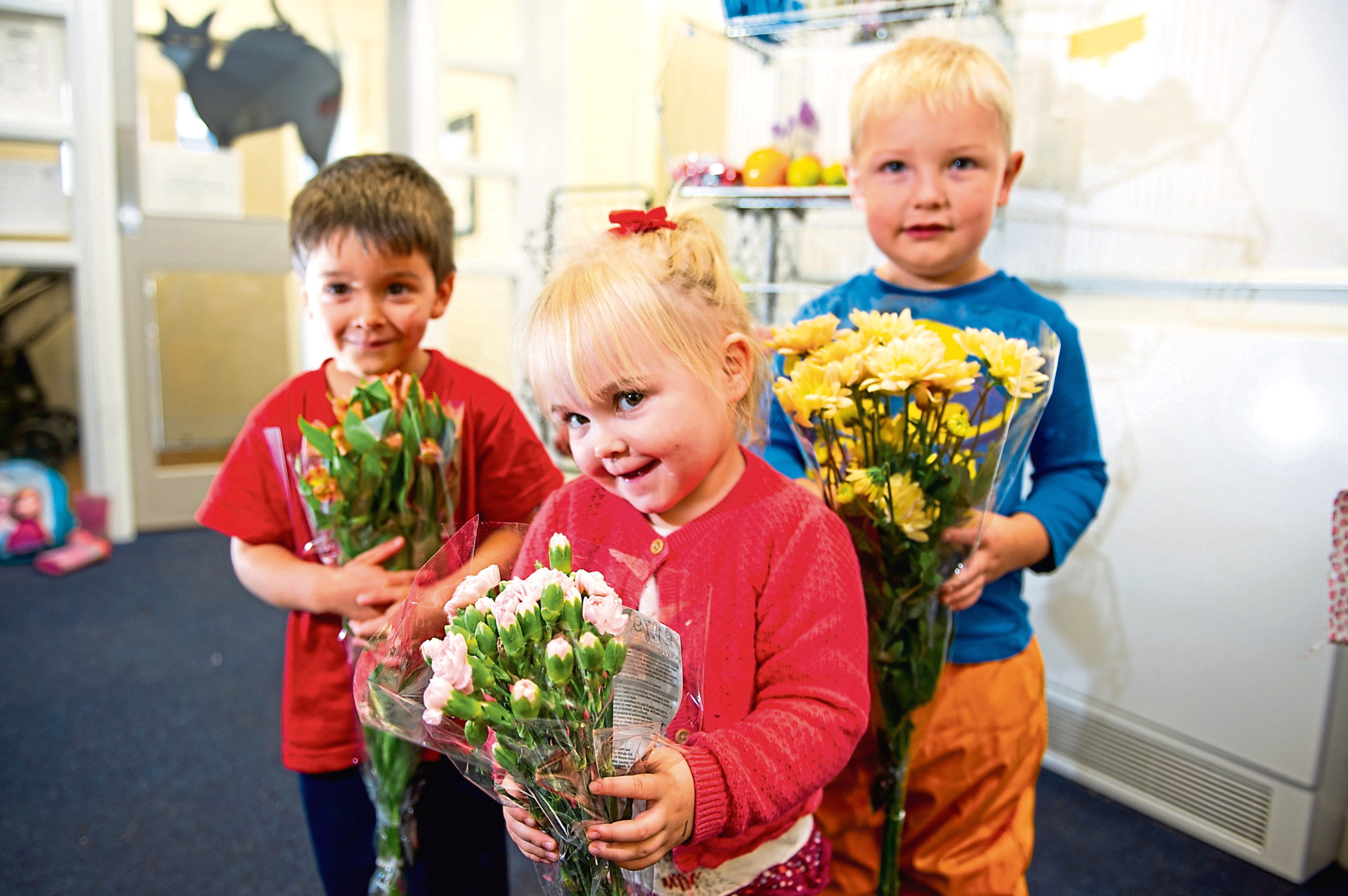 Three of the children at the playgroup with some of the bouquets that they have been leaving anonymously on doorsteps.