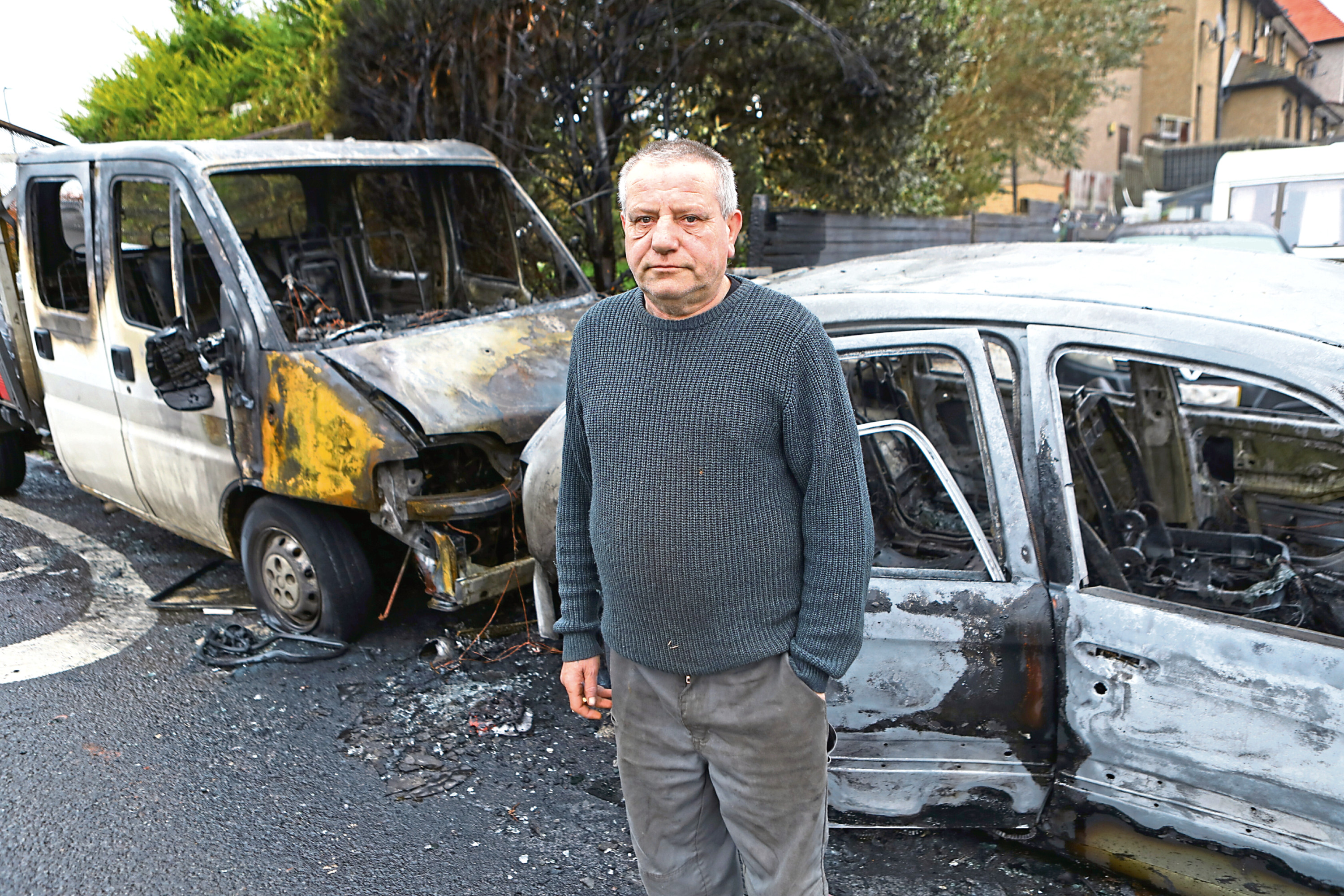 Ian Shand beside the fire damaged car and pick up truck in Dryburgh Place.