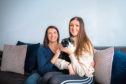 Denise Oudney (left) and daughter Macy Harbut with cat Baxter.