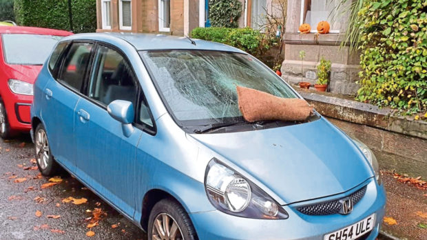 The blue car was spotted with its windscreen smashed by a sandbag after many student parties on Halloween.