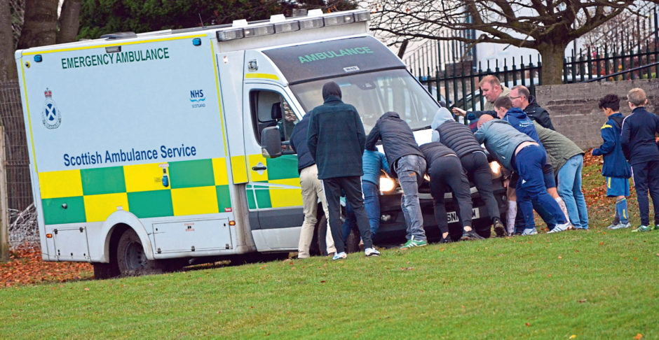 Helpers attempt to push the ambulance out of the mud.
