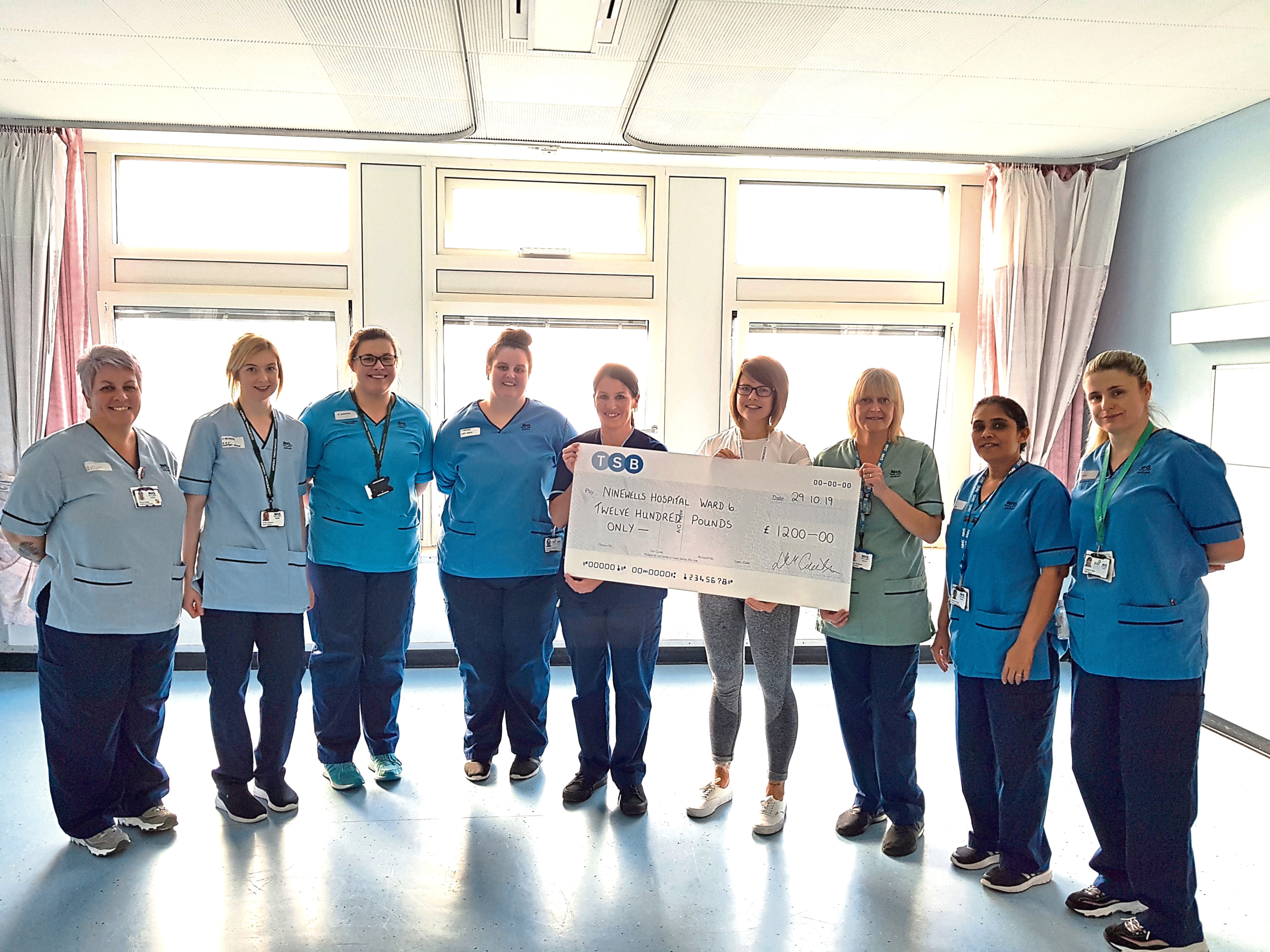 Jena Jamieson Dundee presenting the cheque to staff in Ward 6.