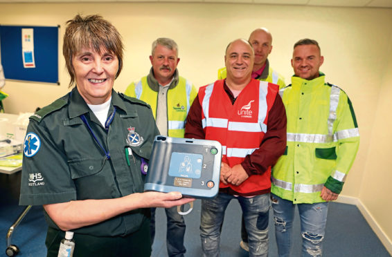 Hazel with Colin (in the red vest), and Paul Drummond, George Millar and Jim Cosgrove, from Tayside Contracts Dundee at the handover.