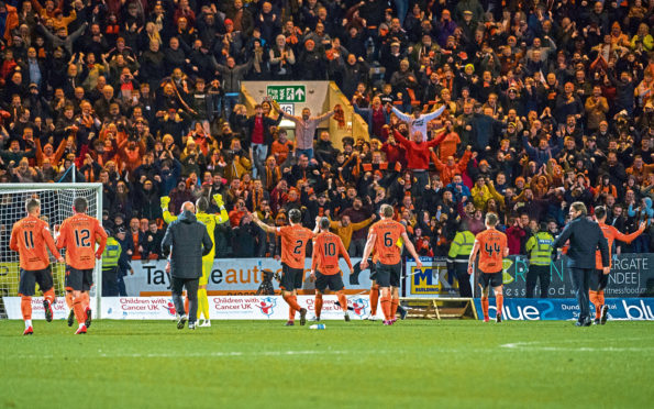 The Dundee United players celebrate in front of the fans at full-time of the match between Dundee FC and Dundee United.