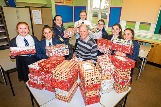 James Gill in the centre surrounded by the shoeboxes and some of the pupils and students that have helped to fill them.
