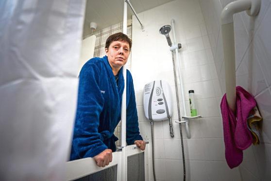 Kerry Bonella beside her faulty shower.