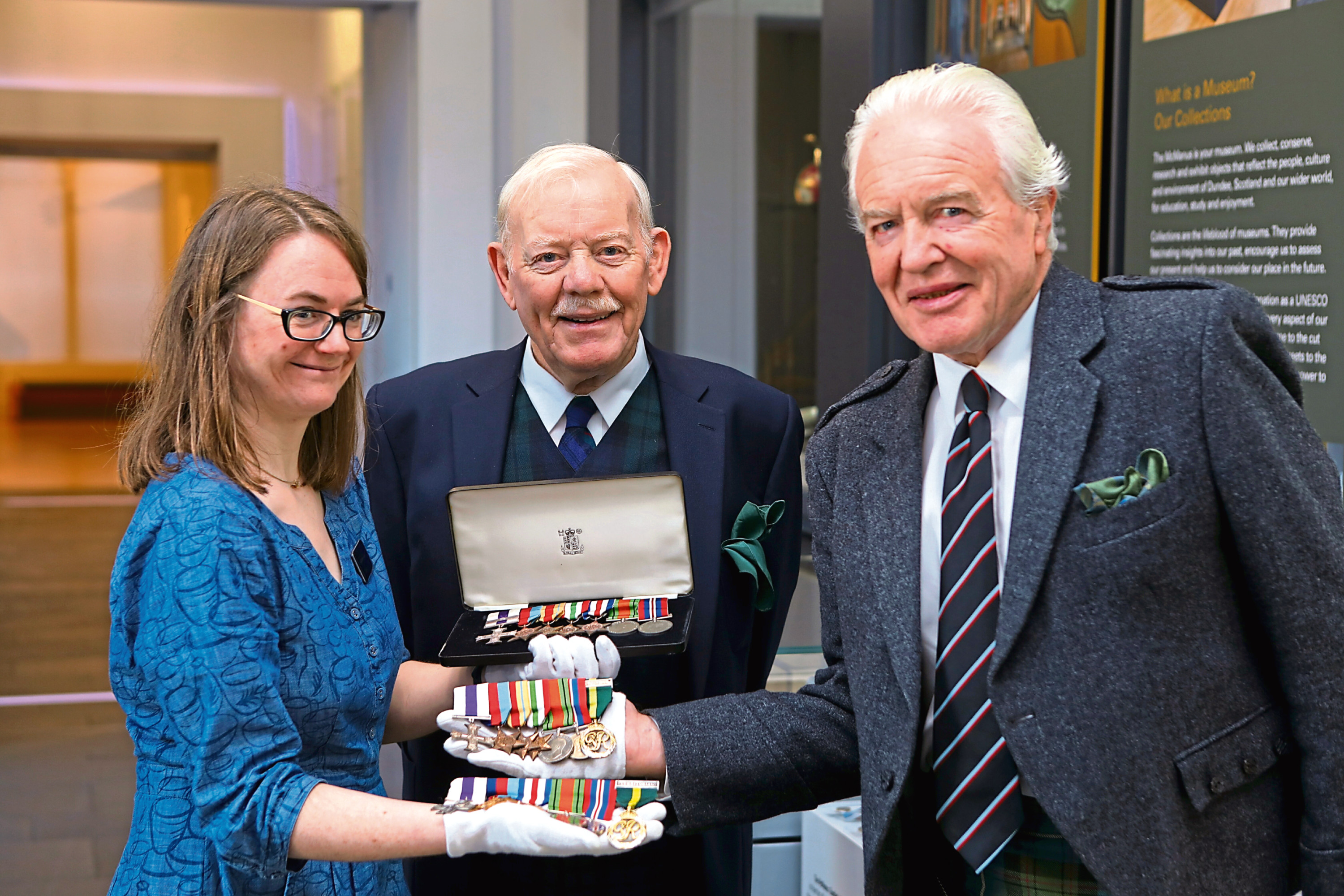 Tele News - Dundee story - Medals handed over to Mcmanus.  CR0016916 Picture shows; Carly Cooper - Curator, with Ian Rae, right, and Sinclair Aitken, centre, Chairman of LACD, holding the medals that were handed over to the McManus Galleris in Dundee today from the Rae family. Friday 29th November 2019. Dougie Nicolson / DCT Media.