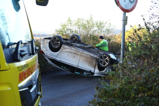The overturned car on the road.
