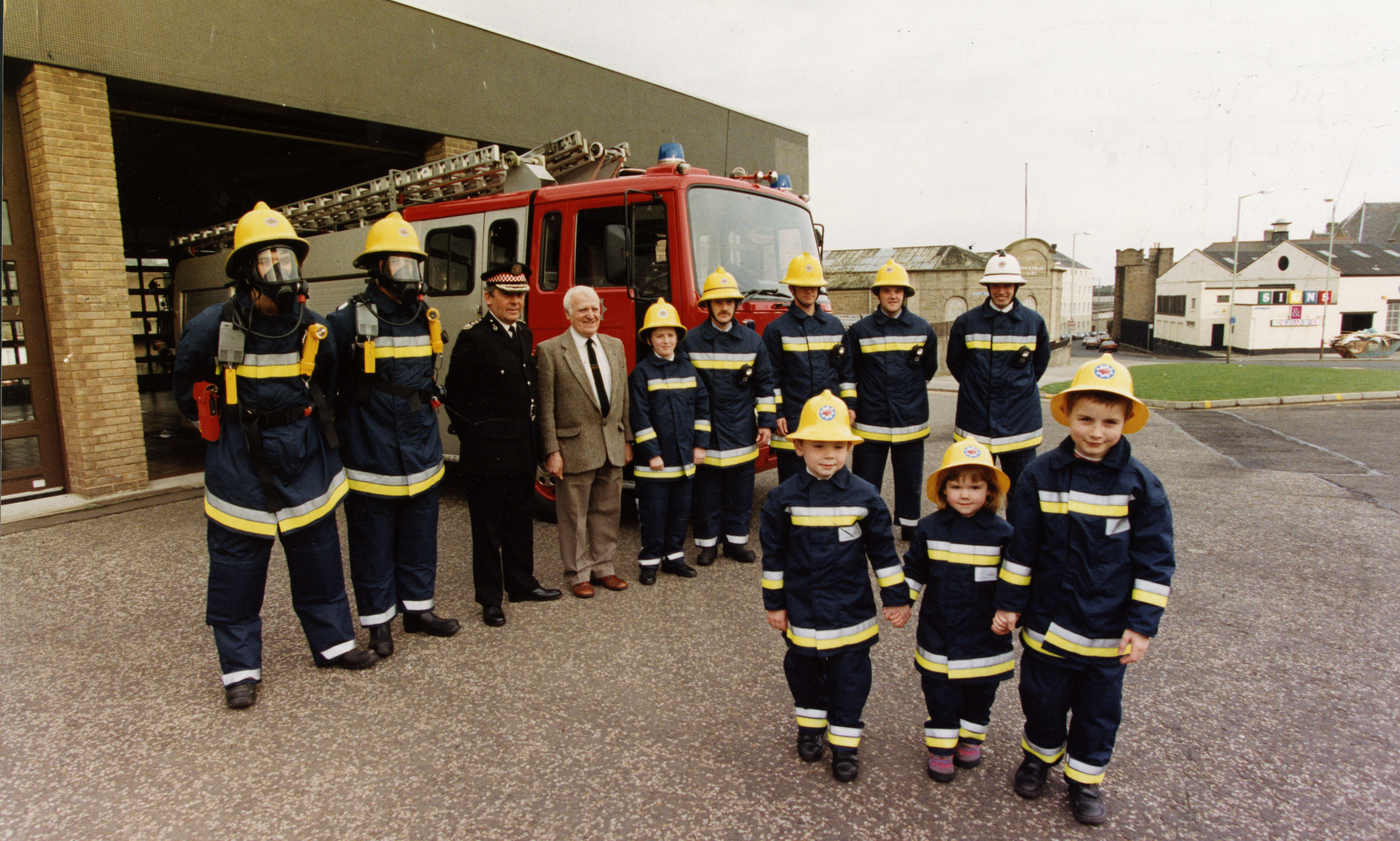 Tayside Fire Brigade model new uniforms at Blackness Road Fire Station, helped by local school children in miniature versions.