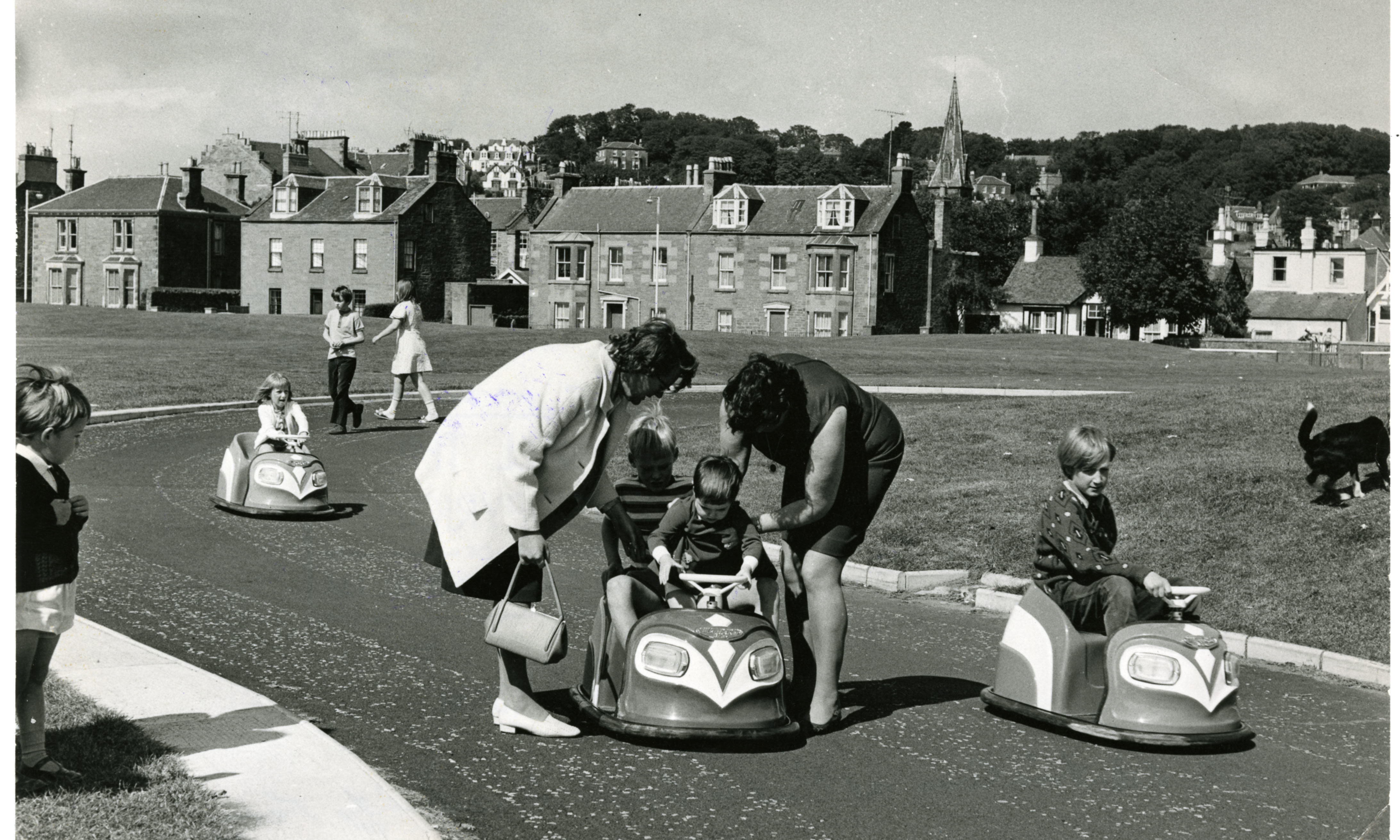 Children driving the electric cars around the race track at Castle Green, Broughty Ferry, while two women help one of the kids into one of the cars. The picture was taken on August 21 1972.