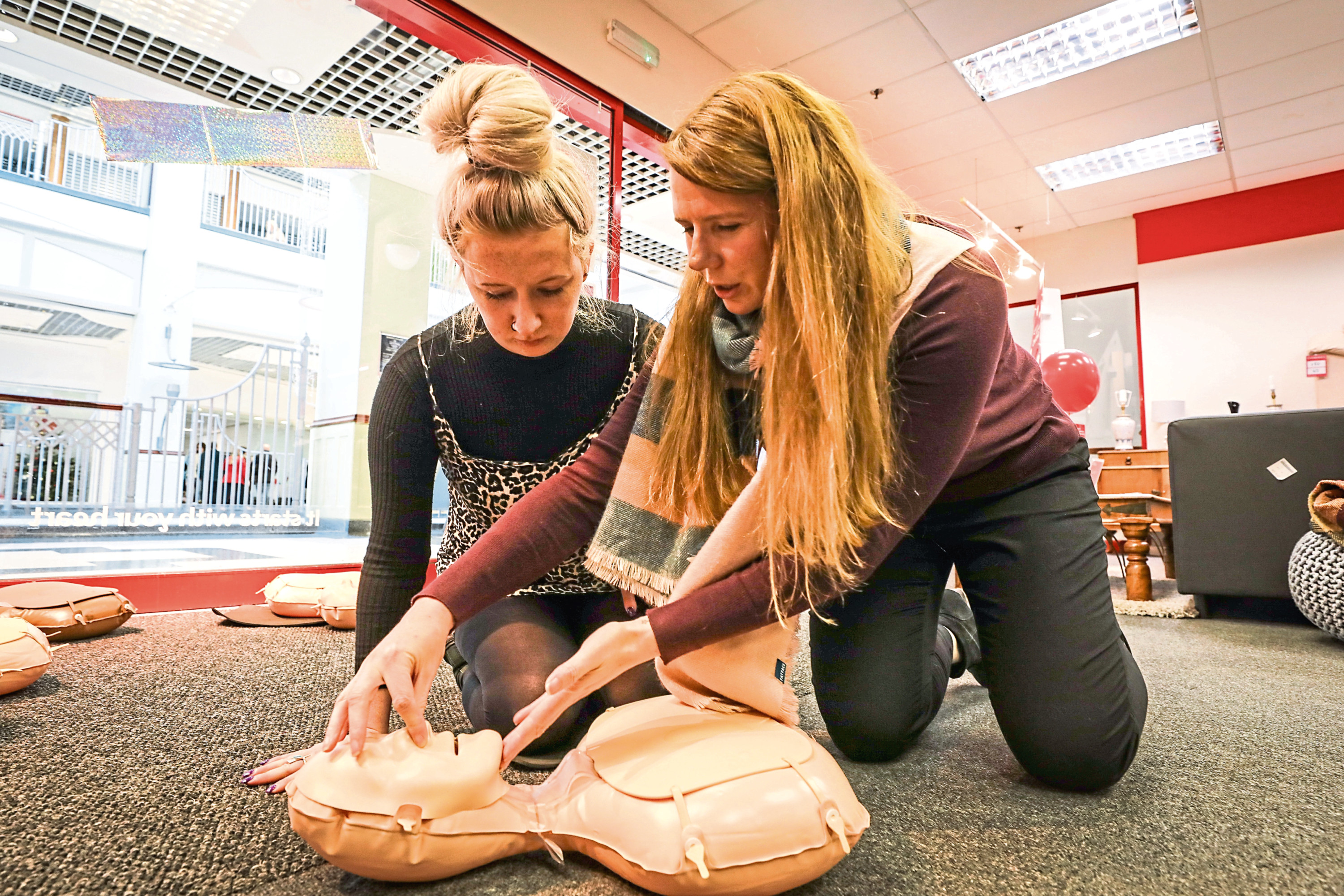 Tele writer Amy getting a demo in how to perform CPR in the British Heart Foundation shop.