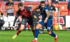 Kane Hemmings and Andrew McDonald of Elgin battle for the ball.