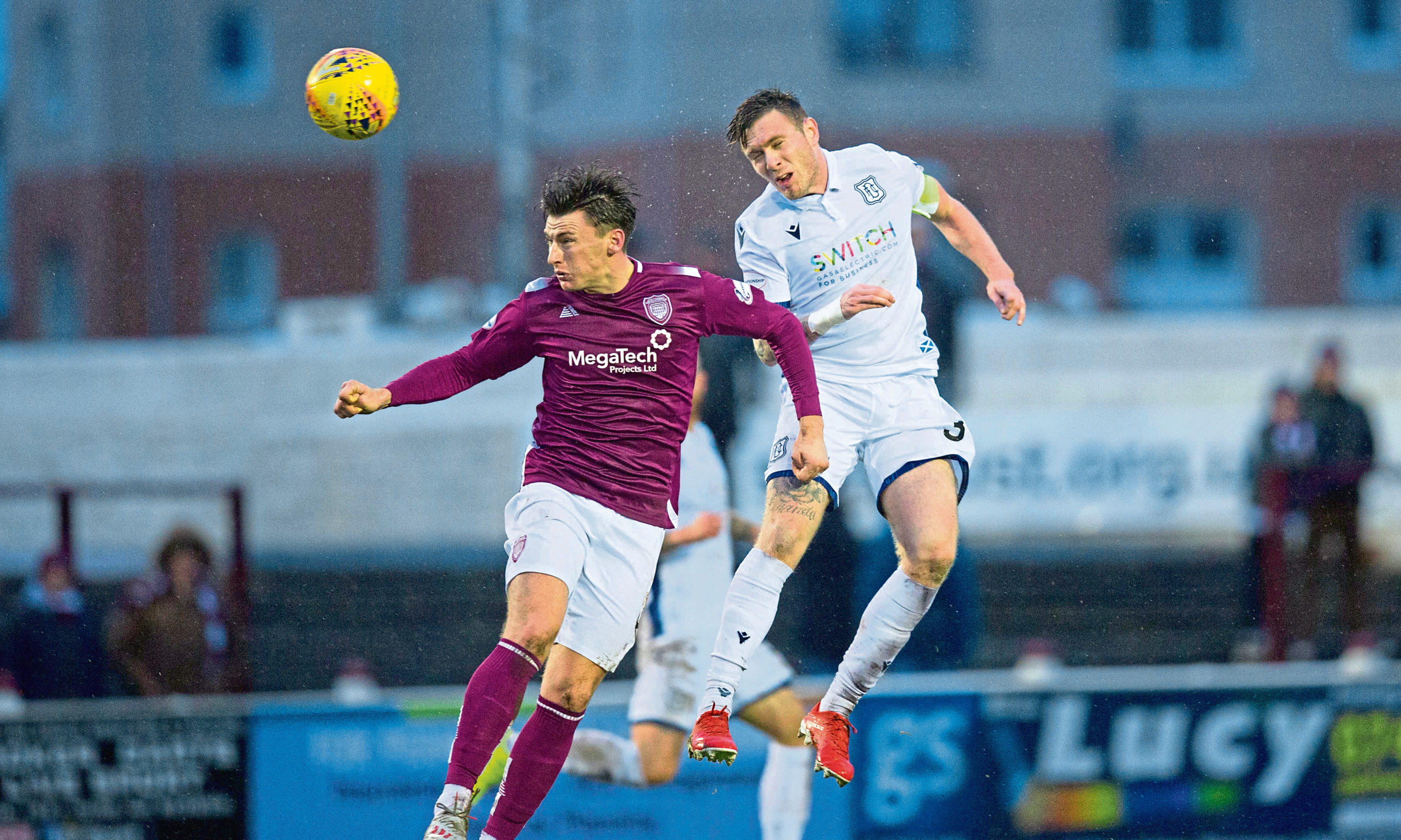 Dundee's Jordan McGhee competes in the air with Michael McKenna of Arbroath at Gayfield on Saturday.