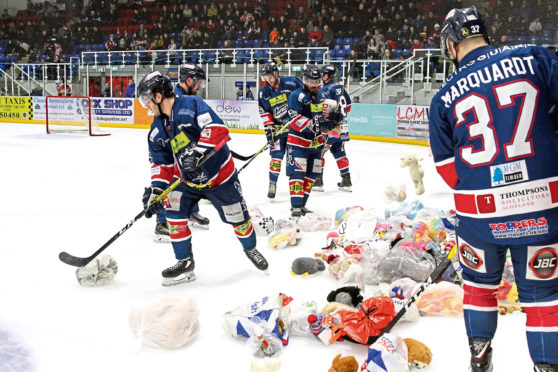 The Stars players gathering up teddy bears on the ice.