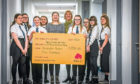 The vocal ensemble presenting the cheque to Victoria Bongiorno, Centre Fundraising Organiser for Maggie's Dundee (middle) with teacher Fiona Anderson (wearing scarf).