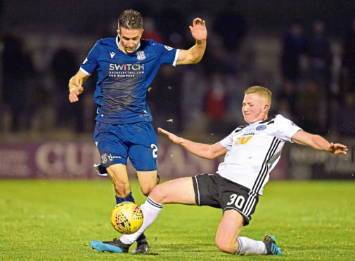 Dundee's Cammy Kerr (left) is tackled by Stephen Kelly during the Ladbrokes Championship match between Ayr United and Dundee at Somerset Park on October 25, 2019.