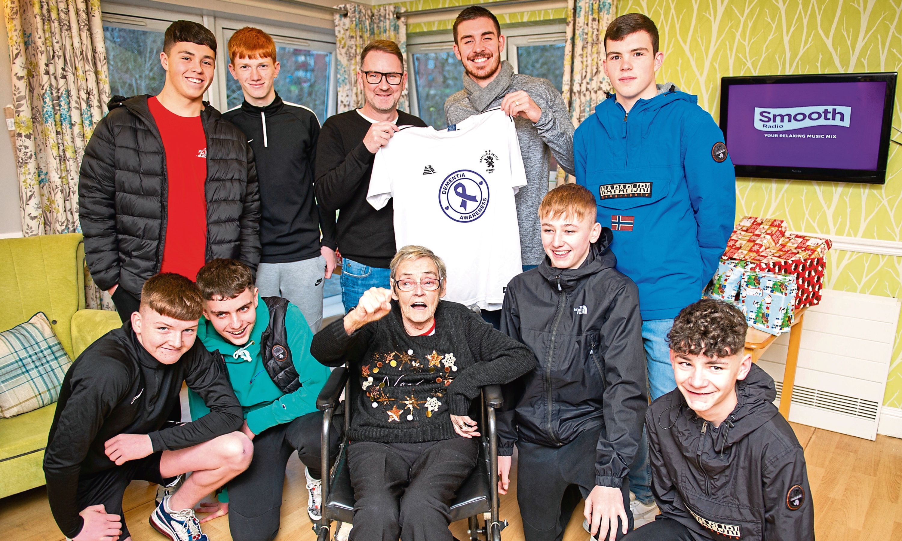 Scott receiving the new kit from Declan, accompanied by some of the players and his mum, Betty.