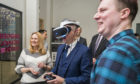 Dr Andrea Szymkowiak and Dr Paul Robertson showcase a VR collaboration with Sony to Derek Mackay in the Emergent Technology Centre at Abertay.