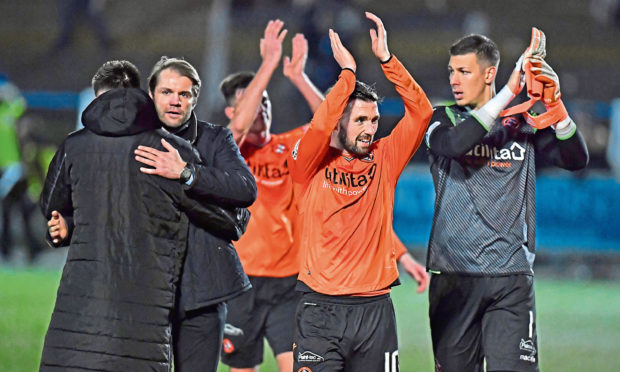 Dundee United manager Robbie Neilson, Nicky Clark, and Benjamin Siegrist applaud the travelling support at full time in Dumfries.