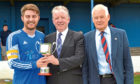 Ally Martin, right, watches as Scott Ritchie, captain of St James, receives the Fairfield Sports and Leisure Trophy from Tom Berry, President of Fairfield Sports and Leisure Club.