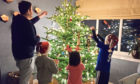 A Carolina House Trust foster carer with their children and foster child getting ready for Christmas.