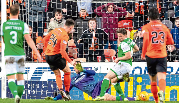 Lawrence Shankland slots home United's first  equaliser against Hibs during the first tie on January 19.