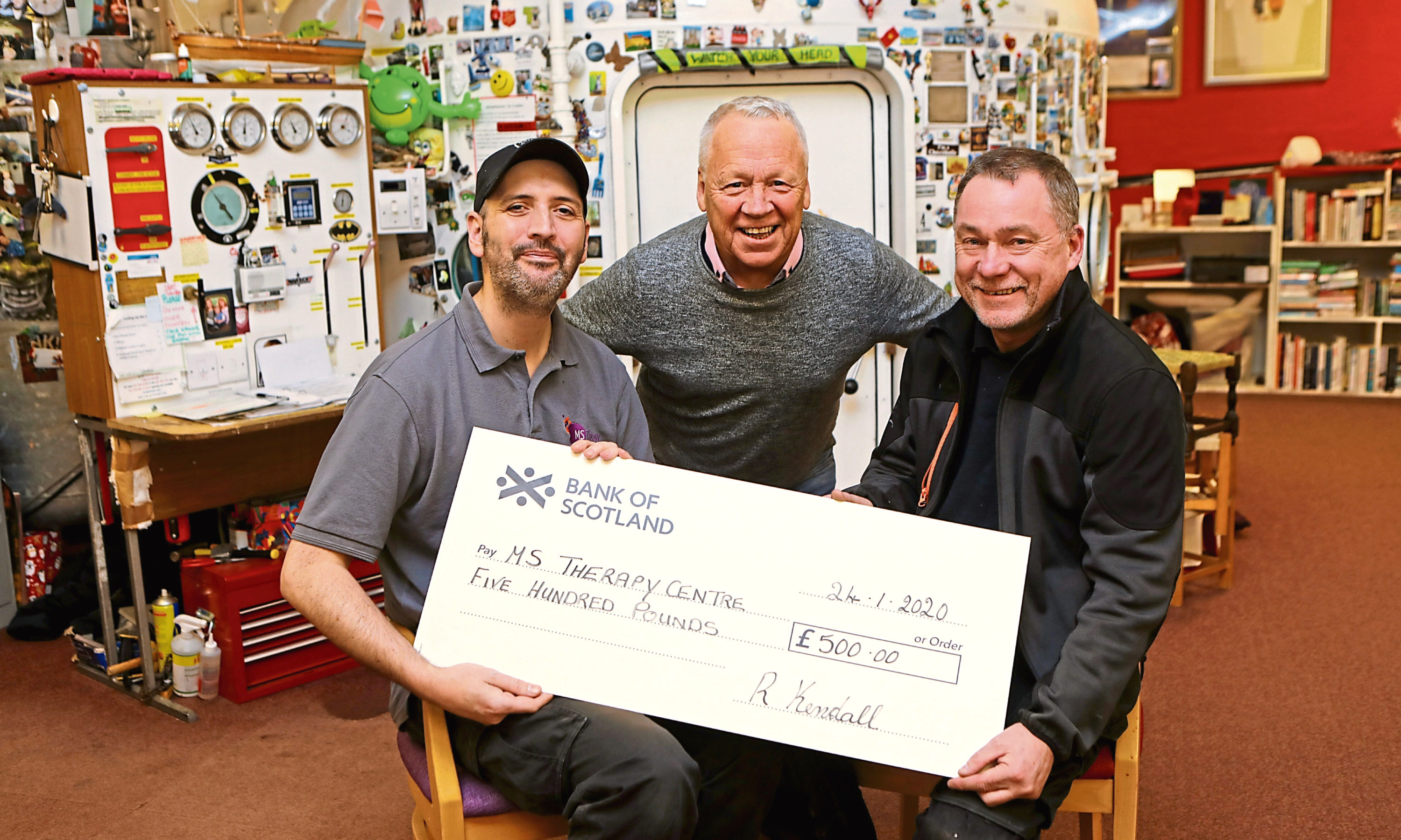 Ross (right) handing over the cheque to Alwyn, as Duncan Fraser, one of Ross's friends, looks on.
