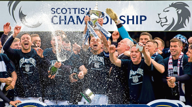 Gavin Rae lifts the trophy to spark the title celebrations at Dens Park as they were crowned winners of the Championship in 2014.