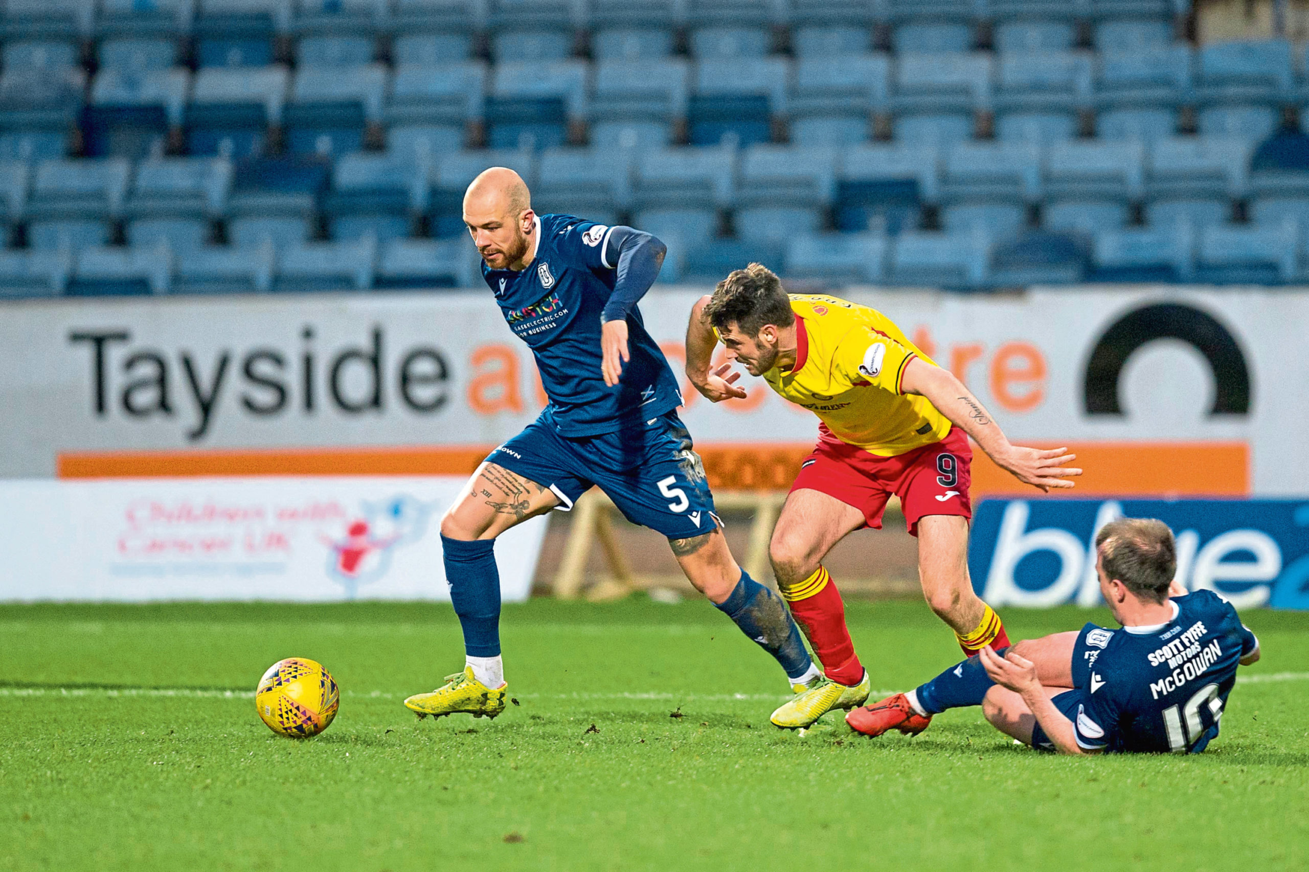 Jordon Forster of Dundee challenges for the ball with Brian Graham of Partick Thistle.