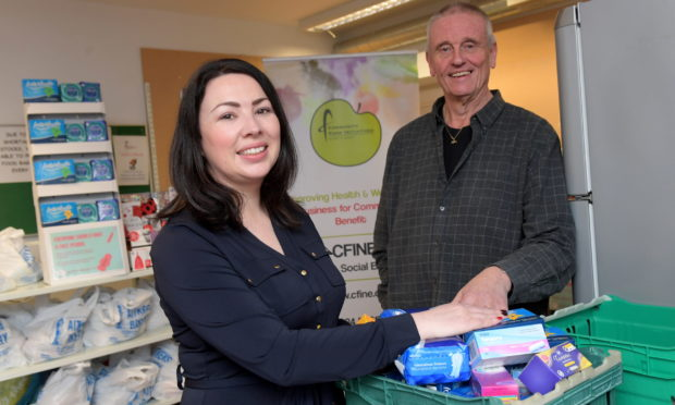 Monica Lennon - seen here at an Aberdeen food bank last month - wants free access to period products enshrined in law.