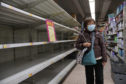 A woman wearing face mask walks past empty shelf of tissue papers at supermarket in Hong Kong.
