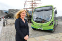 Christine McGlasson - MD of Xplore Dundee beside one of the firm's buses.