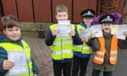 Four pupils ready to give warnings about the parking outside the school, using the handmade tickets.