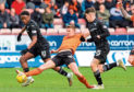 Dundee United's Paul Watson clears the ball away from Jonathan Afolabi during a Ladbrokes Championship match between Dunfermline Athletic and Dundee United.