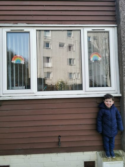Harris, 3, with his two rainbows in the window.