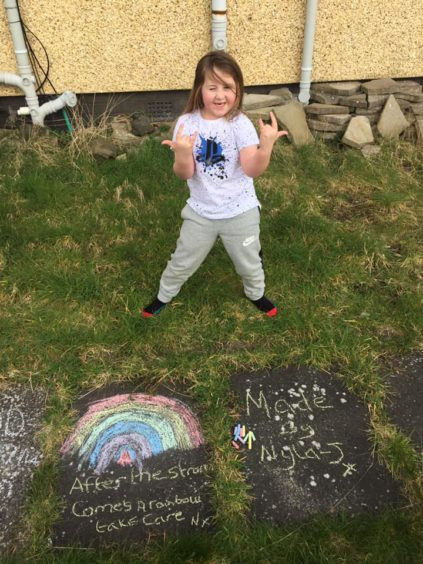 Nyla-j, 6, drew a chalk rainbow in the garden while mum Jenna Nairn was hanging the washing out.