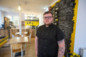 Daniel Cashley in his restaurant where he is still able to provide takeaway meals.
