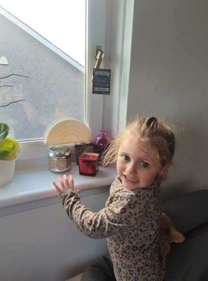 Willow, aged 3, with her picture in the window.