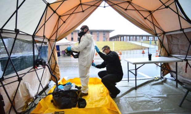 Sgt. First Class Mason Lord, with the Vermont Army National Guard, helps remove a personal protective equipment suit in a decontamination zone at the Covid-19 testing facility in a parking lot in Vermont.