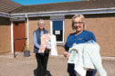 Susan, left, handing over some of the bags to home manager June McCarroll.