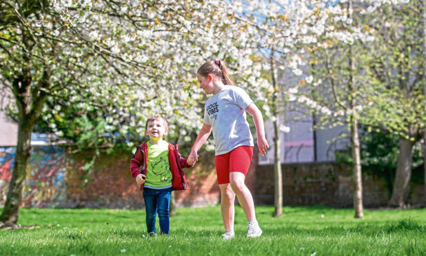 Theo, 4, and Ellie, 9, Etchels enjoy the spring blossom while out for their daily excecise in Hilltown Park.