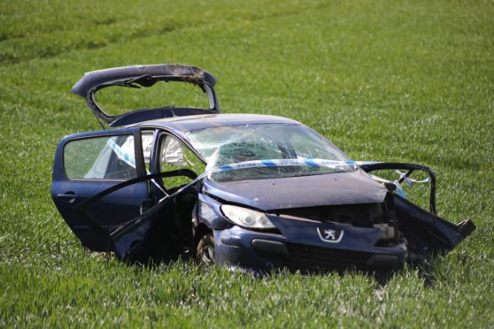Evening telegraph/courier news CR000 G Jennings pics, blue Peugot crashed in a farm field just outside Arbroath on the Montrose road, friday 17th april.